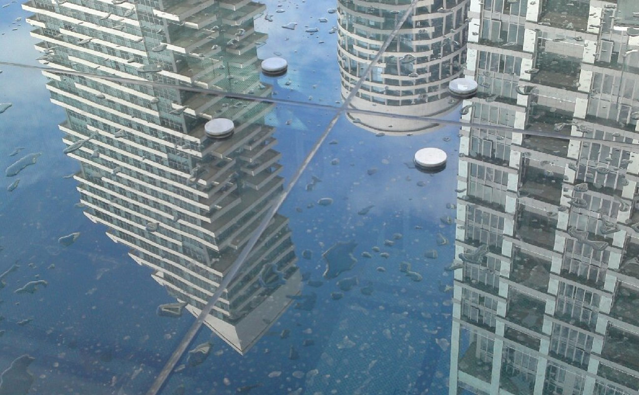 building exterior, architecture, built structure, city, reflection, modern, glass - material, building, water, skyscraper, office building, window, low angle view, day, puddle, tall - high, wet, tower, outdoors, sky