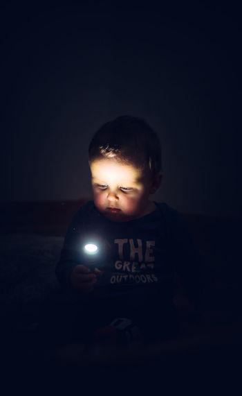 Cute boy holding flashlight sitting outdoors at night