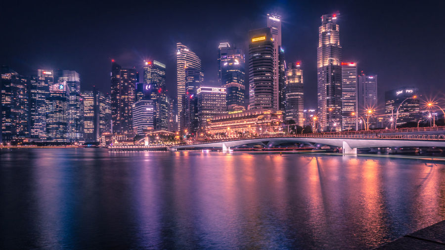 A beautiful night view of singapore in front of fullerton hotel Architecture Building Building Exterior Built Structure City City Life Cityscape Financial District  Illuminated Landscape Modern Night Nightlife No People Office Building Exterior Outdoors Reflection Sky Skyscraper Transportation Travel Destinations Urban Skyline Water The Still Life Photographer - 2018 EyeEm Awards