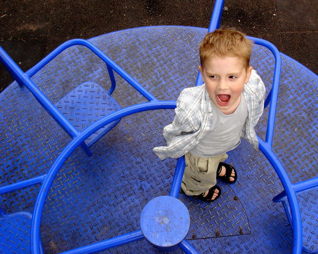 High angle view of boy with mouth open standing on blue merry-go-round