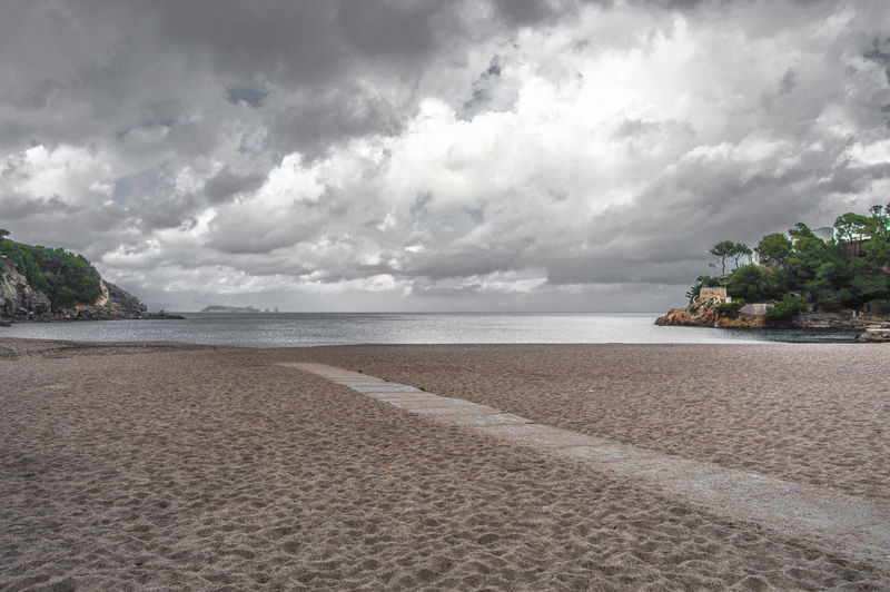 Scenic view of beach and sea against cloudy sky