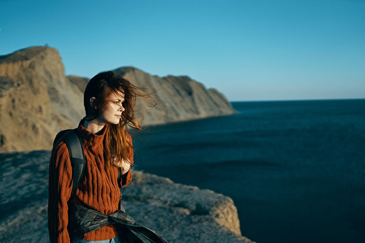 Young woman standing on rock by sea against clear sky