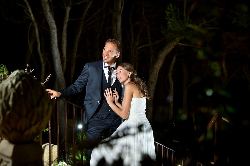 Wedding Couple Standing By Railing At Night