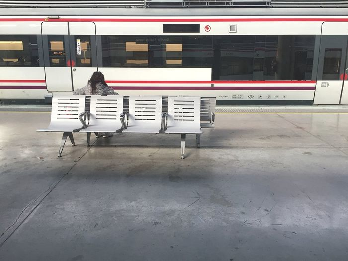 Rear View Of Passenger Sitting On Bench Against Train At Railroad Station
