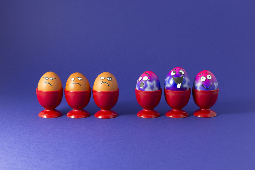 Group of colorful painted Easter eggs with funny cartoon style faces and group of grumpy looking brown eggs in red plastic egg cups on purple background Celebration Easter Easter Egg Easter Eggs Fun Happy Background Cartoon Close-up Colored Background Contrast Crazy Discrimination Eggcup Envy Face In A Row Multi Colored No People Party Purple Red Season  Studio Shot Style