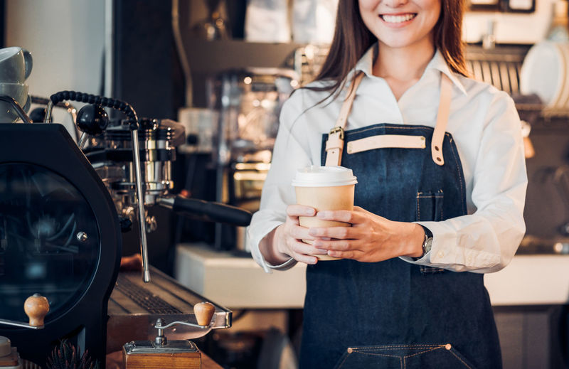Close up on coffee take away cup with asian woman owner barista holding mug with two hand with smiling face at cafe bar background,Focus on coffee up Jeans Service Waitress Woman Asian Girl Bar Barista Cafe Coffee Cup Coffee Shop Drink Food And Drink Food And Drink Industry Indoors  Occupation Preparation  Real People Refreshment Restaurant Service Small Business Smile Standing Take Away Coffee Women