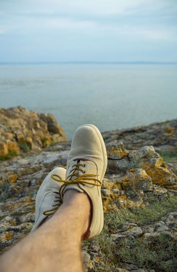 Low section of person on rock by sea against sky