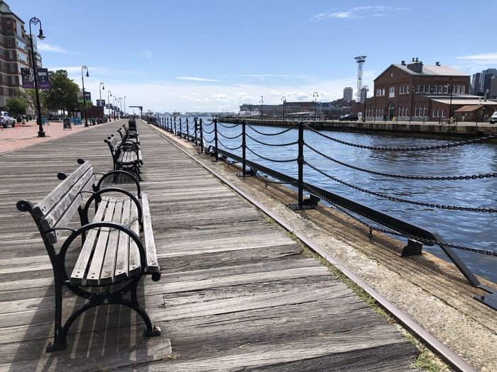 Empty bench by river in city against sky