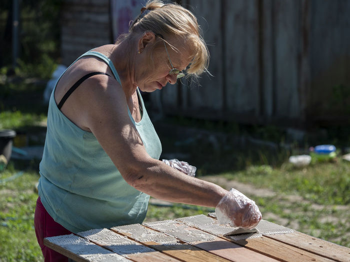 Side view of senior woman painting wooden table in yard