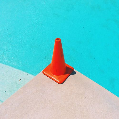 High Angle View Of Orange Traffic Cone By Swimming Pool