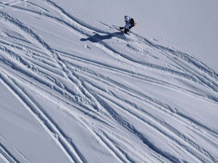 High angle view of person skiing downhill on snow
