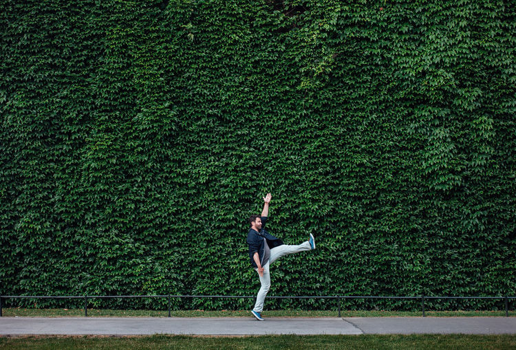 Side View Of Young Man Jumping On Footpath By Ivy Wall