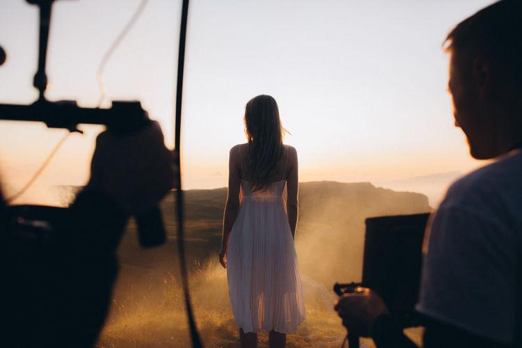 Photographers and model in desert against sky during sunset