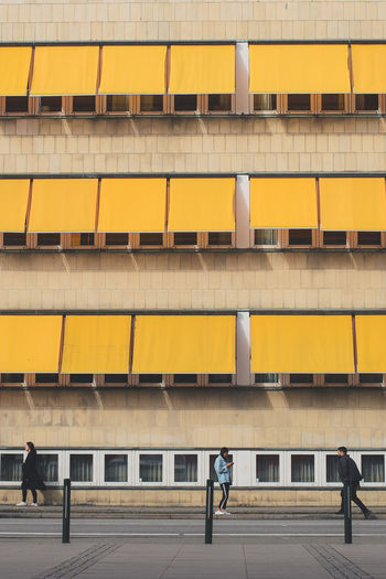 Three Objects Three People EyeEmNewHere Architecture Building Building Exterior Built Structure City Outdoors People Walking Window Yellow The Architect - 2018 EyeEm Awards #urbanana: The Urban Playground Summer In The City