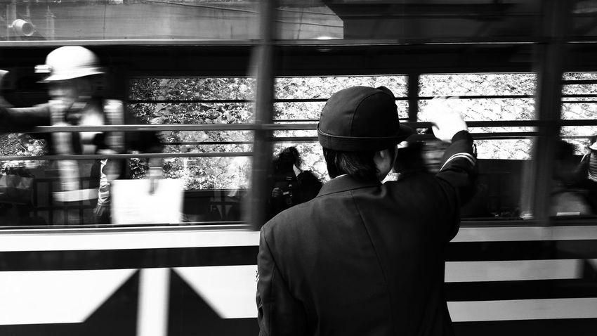 Waving to passenger and wait for next train coming. EyeEmNewHere Black And White OSAKA Japan Say Goodbye Waving Bye Hardwork Indoors  Job Occupation Train Station Women Working Business Stories