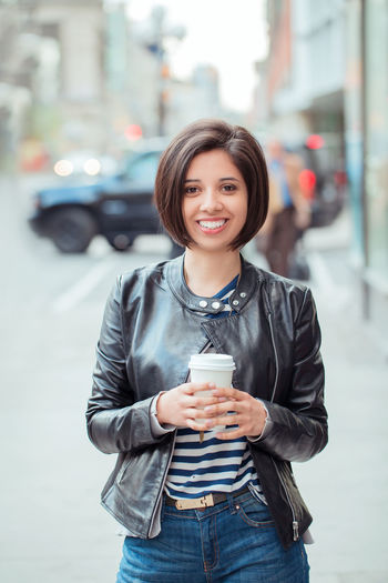 Portrait of smiling young woman holding disposable cup in city