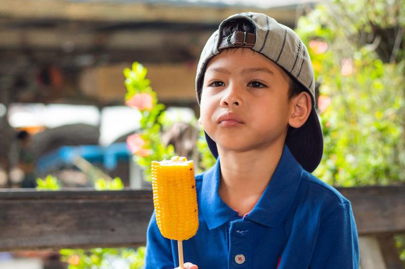 Close-up of boy eating corn