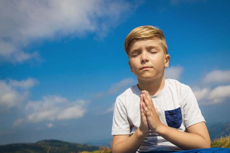 Small boy in namaste pose meditating with eyes closed in nature against the sky. copy space.
