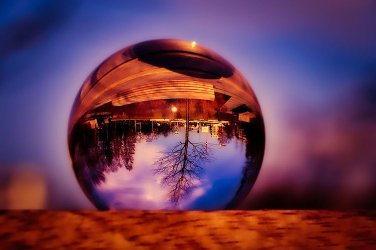 Close-up of crystal ball against sky during sunset