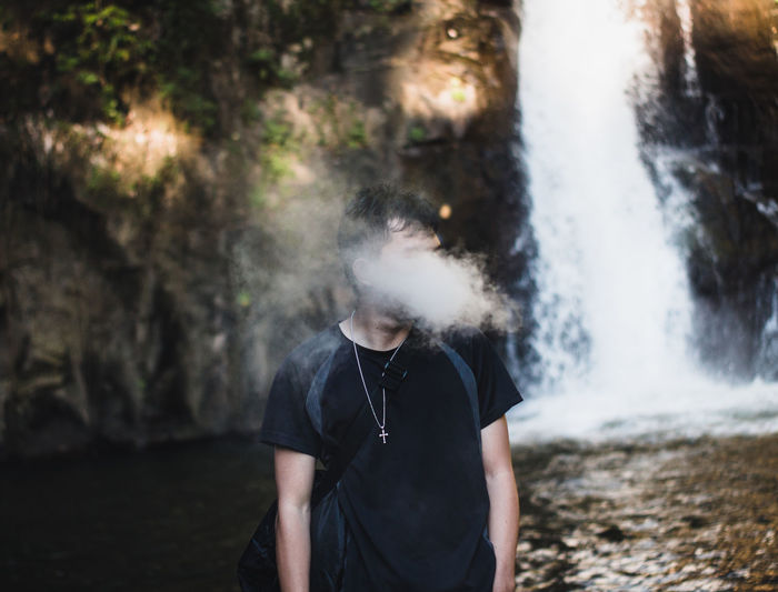 Full length of man standing in water and smoke vape