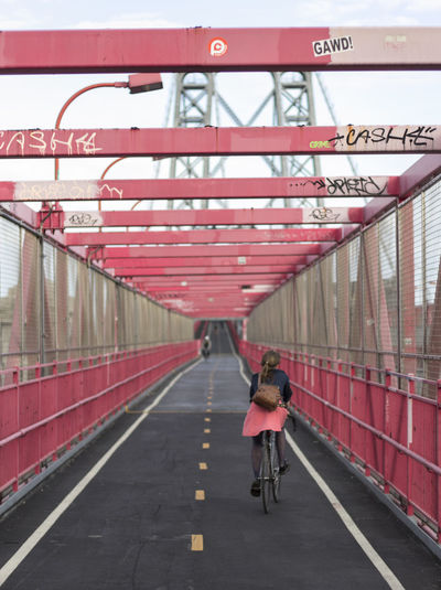 Brooklyn Colour Your Horizn NYC New York Pink Williamsburg Bridge Architecture Bicycle Bridge - Man Made Structure Connection Cycling Day Land Vehicle Lifestyles Mode Of Transport One Person Outdoors Pink Color Public Transportation Real People Rear View Red Transportation Travel Women