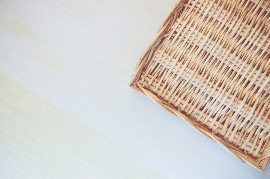 wicker basket on a light wood surface Abstract Comfortable Common Object Communication Copy Space Cropped Design Everyday Objects Ideas Indoors  Order Simplicity Single Object Still Life Studio Shot Table Wall White Background Wicker Basket Wooden Light