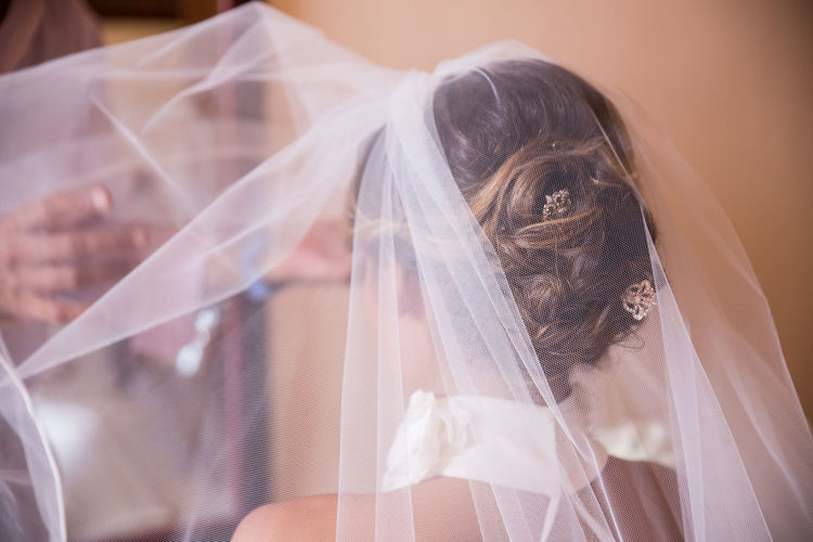 Cropped image of friend putting veil on bride