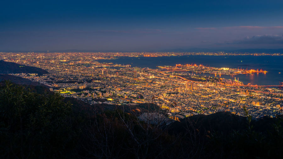 """View of several Japanese cities in the Kansai region from Mt. Maya. The view is designated a """"Ten Million Dollar Night View."""" OSAKA Observation Point Twilight Beauty In Nature Cityscape Dusk Illuminated Kansai Kobe Landscape Mountain Nature Night No People Ocean Outdoors Scenics Sea Sky Tranquility Travel Destinations Tree Urban Skyline Viewpoint"""
