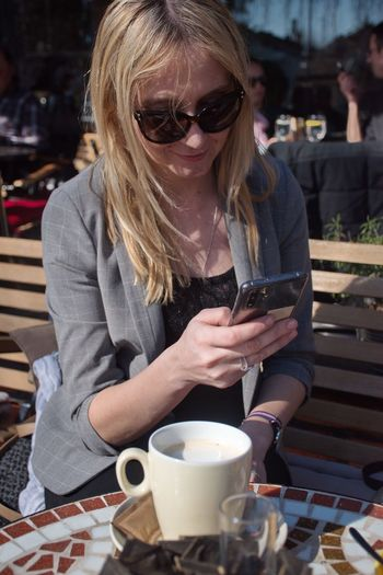 Blond Hair Communication Technology Mobile Device Mobile Phone Phone Cup Coffee Cup Coffee Sitting Woman Glasses Food And Drink Drink Sunglasses Refreshment Cafe One Person