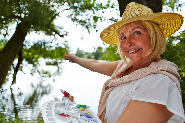 Portrait of happy woman holding hat against trees