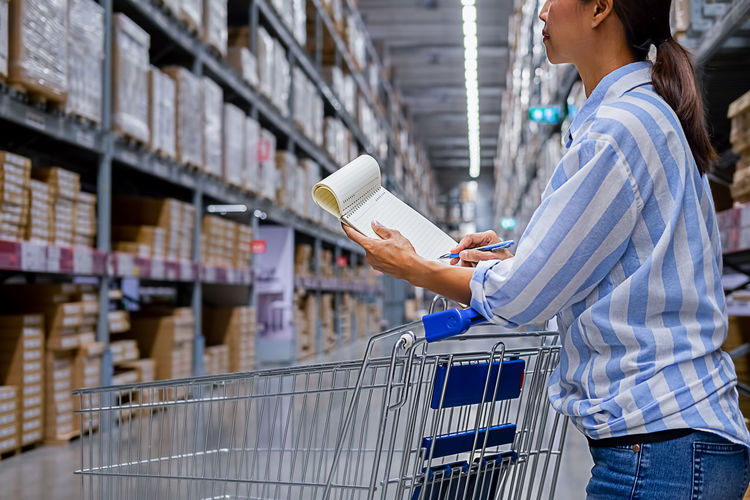 Midsection of woman writing while standing in warehouse