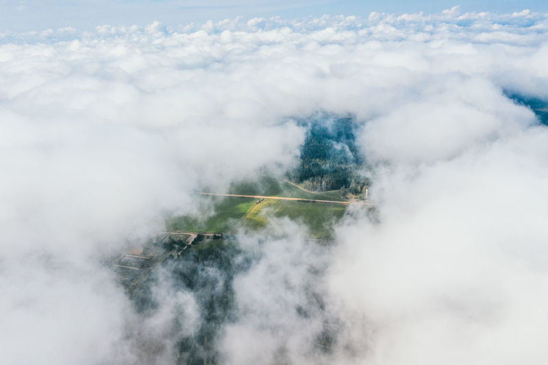 High flight in the cumulus clouds over agricultural fields in summer.