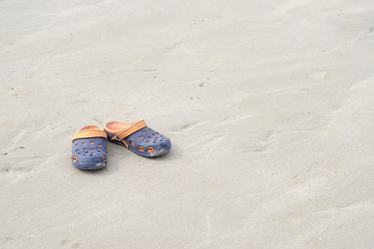 Close-up of sandals on sand at beach