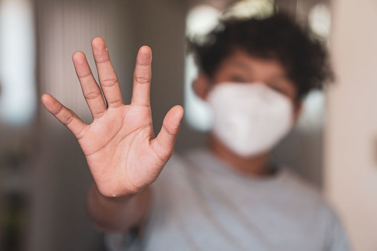 Close-up of boy showing stop gesture while wearing mask