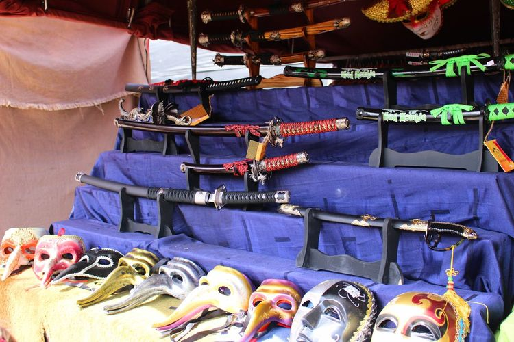 High angle view of masks and swords for sale at market
