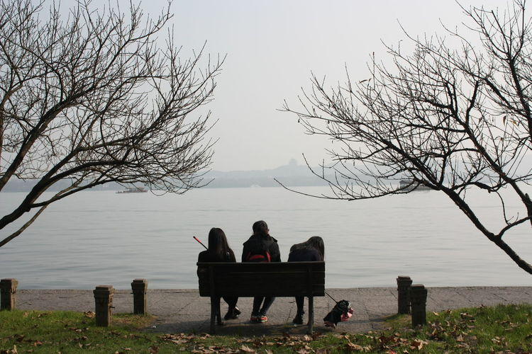 People sitting on bench by lake