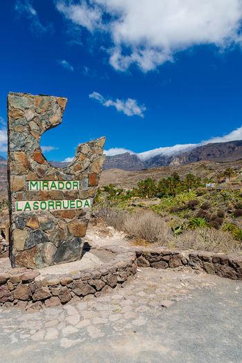 Information sign on landscape against blue sky