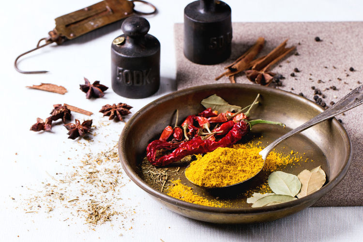 Spices turmeric and dry reh hot chili peppers on metal plate, srved over white tablecloth with vintage weight. Anise Bay Leaves Chili Pepper Cinnamon Curcuma Food Plate Seasoning Spices Spicy Spoon Textile Turmeric  Turmeric Powder Vintage Weight White Yellow