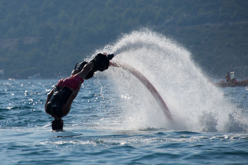 Man Flyboarding In Sea Against Mountains