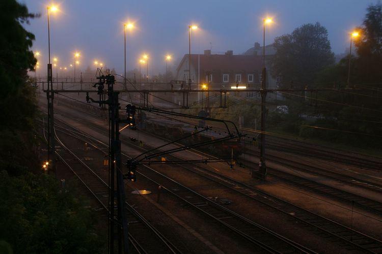 Illuminated railroad tracks at dusk