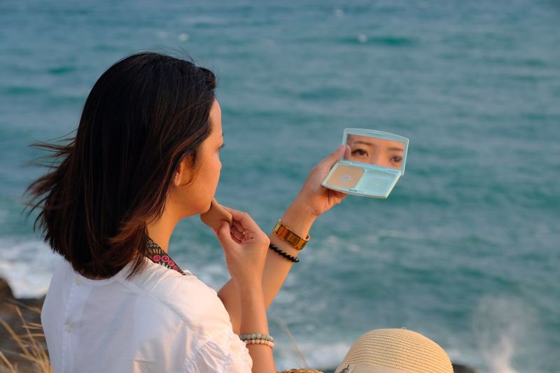 Side view of woman applying make-up sitting by sea