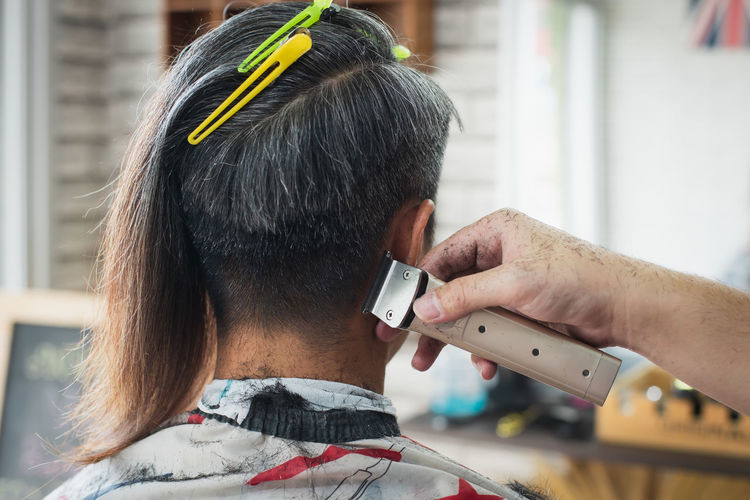 Cropped hand of barber cutting hair of customer