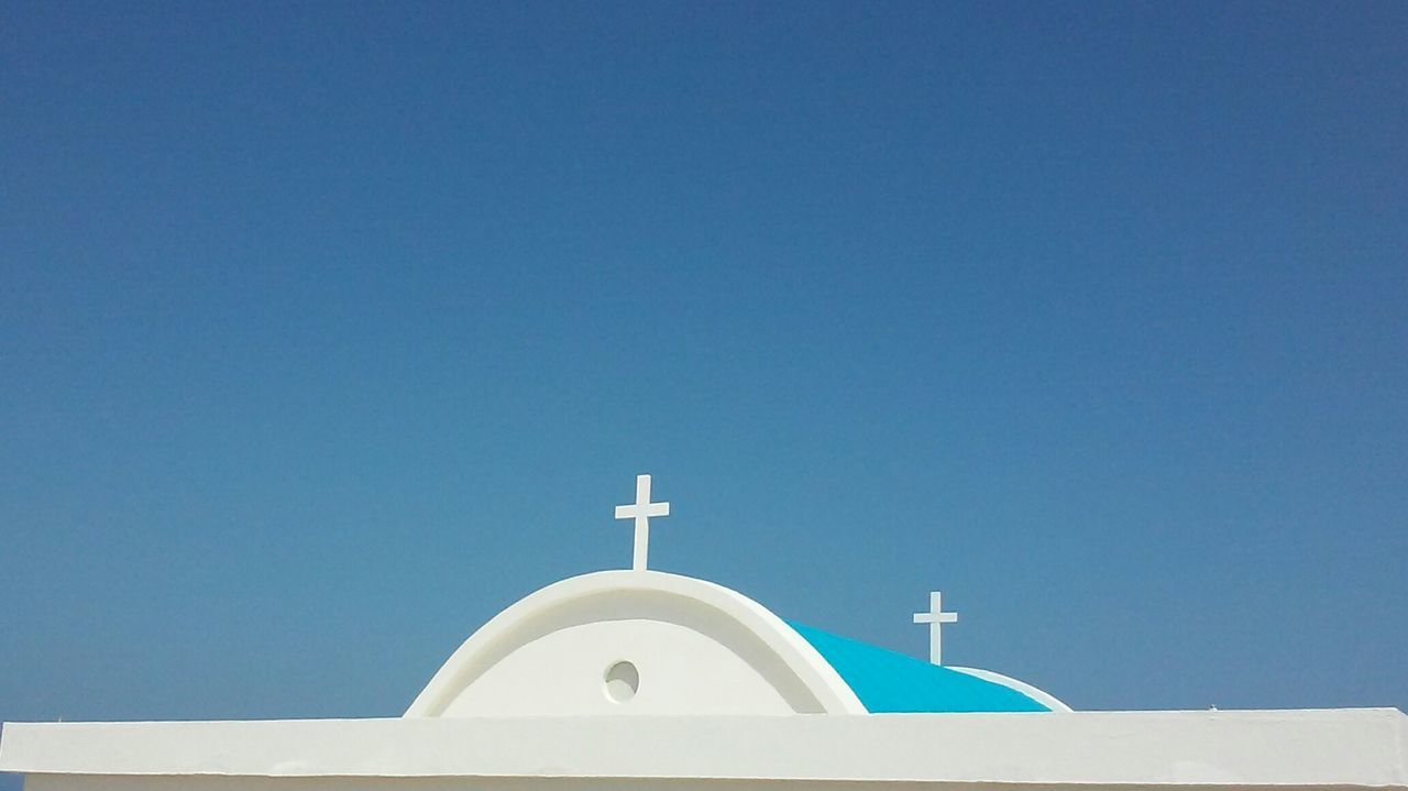 religion, spirituality, cross, copy space, clear sky, place of worship, built structure, white color, blue, building exterior, no people, day, architecture, outdoors, whitewashed, bell tower