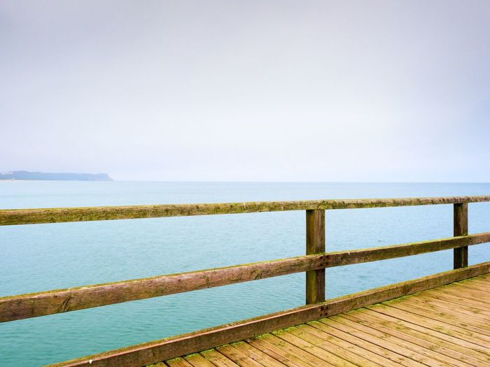 Wooden railing by sea against clear sky