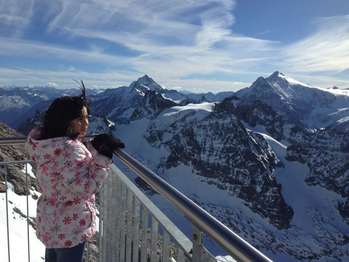Teenage Girl Standing At Observation Point Against Snowcapped Mountains
