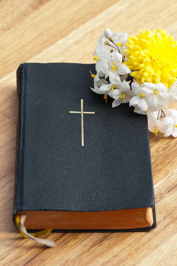 Flower Flowering Plant Book Table Indoors  Publication Close-up No People Plant Wood - Material Education Still Life High Angle View Wood Freshness Text Preparation  Black Color Note Pad Leather Studying Cross Holy Cross Bible Christianity Confirmation Confirmation Day Communion Belief Religion Religion And Beliefs Religion And Tradition