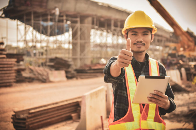 Portrait of architect holding digital tablet showing thumbs up at site