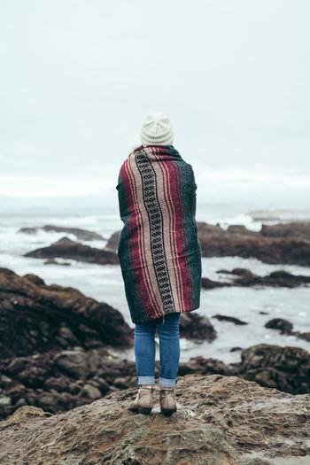 A young woman looks out at the ocean while bundled in a blanket. Active Beach Blanket California Coastline Cold Contemplation Dramatic Fun Hiking Hipster Millenials Modern Moody Ocean Pondering Rainy Days Snuggles Thinking Vacations Warm Water Winter Woman Young
