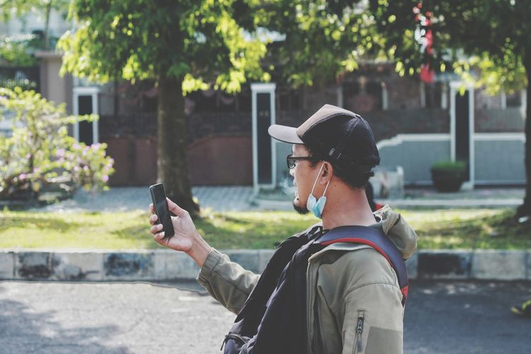 Side view of man photographing with mobile phone