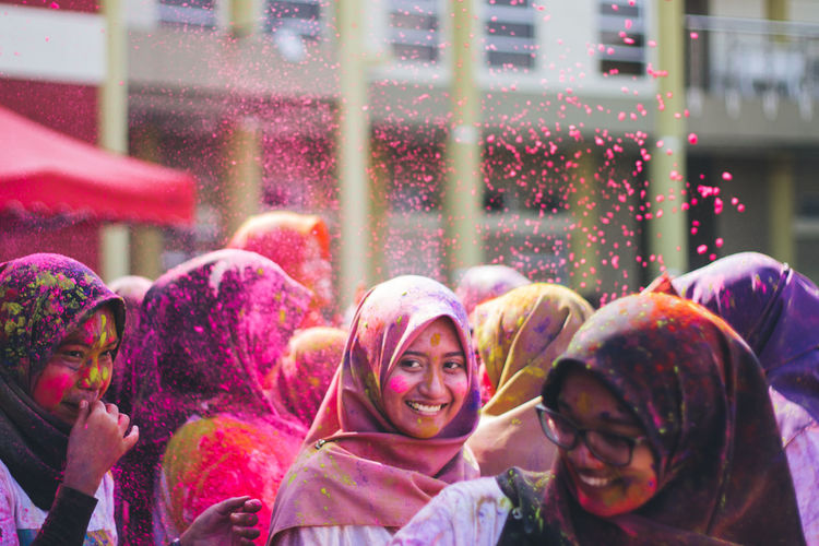 Smiling friends in hijab playing with power paints during holi